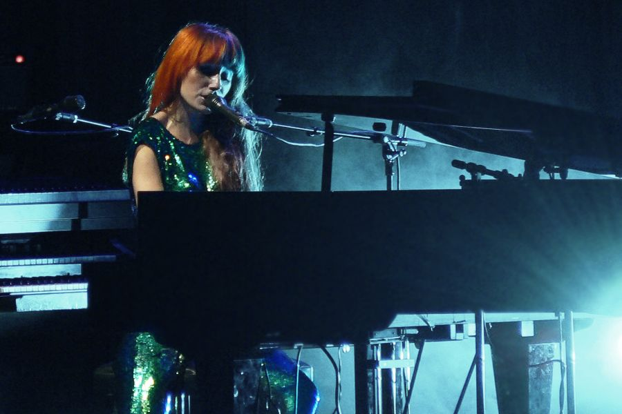 Tori Amos sitting behind a grand piano performing