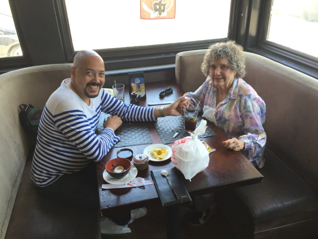 A younger man and older woman are in a booth at a restaurant. They hold hands across the table.