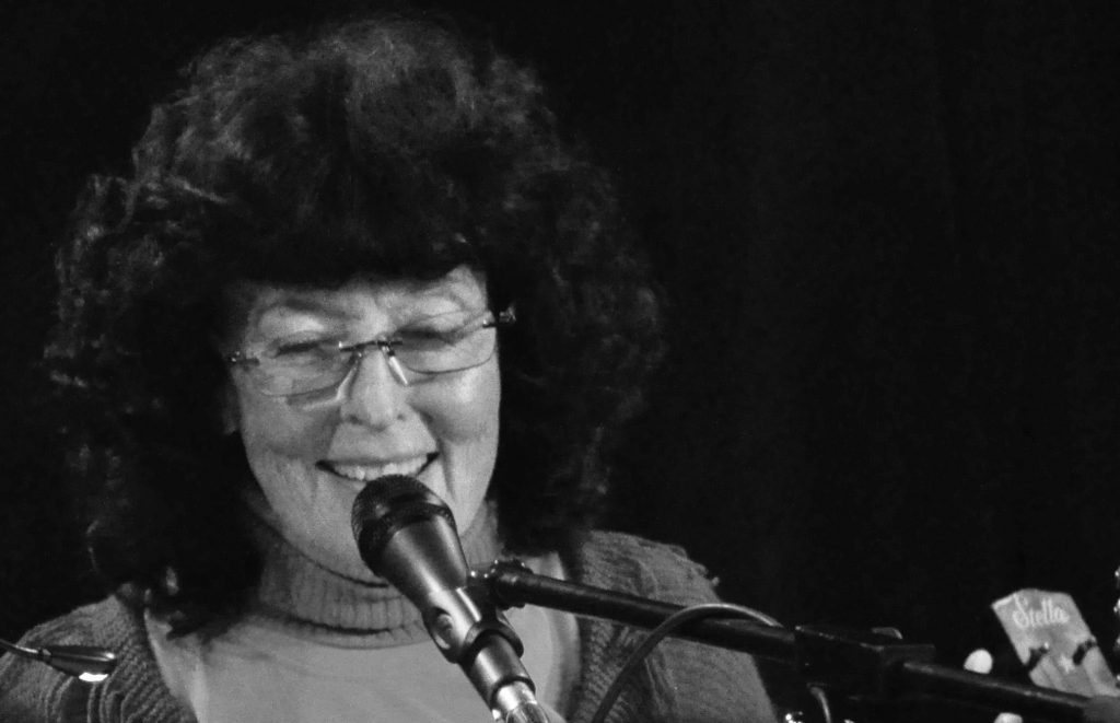 Black and white photo of Linda Perhacs speaking or singing into a microphone.