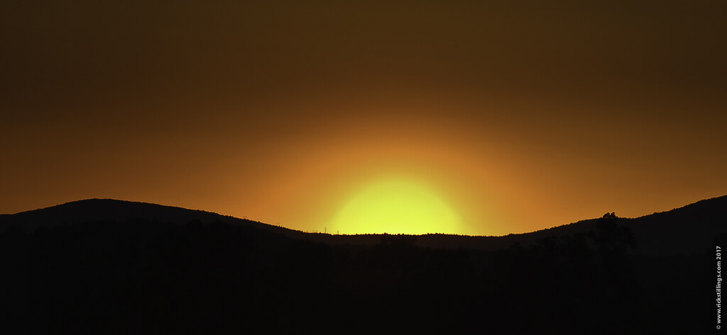 sunset over a hill or mountain