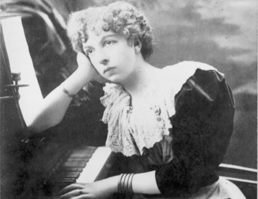 Cécile Chaminade leaning her elbow over a piano and looking off to the left. The photo is in black and white.